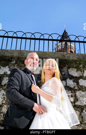 Wedding concept. A handsome married couple stands by the white stone wall, Lovely people looking in the distance and posing towards for the camera. - Stock Photo