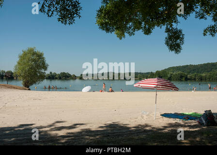 The Lac des Varennes at Marcon, Pays de la Loire, with swimming and canoeing. Sunshine, blue skies with golden sand and colourful beach umbrellas. - Stock Photo