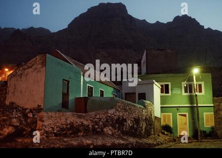 Santo Antao Island, Cape Verde - Jan 5 2016: village at night with the ever so typical colorful buildings underneath the towering cliffs - Stock Photo
