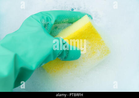 A hand in a turquoise glove holds a sponge for washing dishes in a copious foam. Close-up - Stock Photo