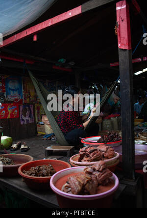 Cambodian woman on a hammock selling pork meat in a market, Phnom Penh province, Phnom Penh, Cambodia - Stock Photo