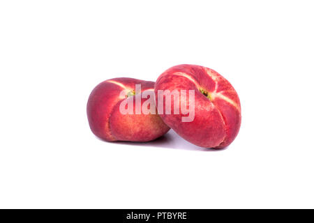 Two fresh red flat peaches on a white background - Stock Photo