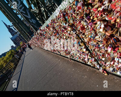 The pedestrian walkway on the famous Hohenzollern Railway Bridge in Cologne has thousands of love padlocks attached to the fence - Stock Photo