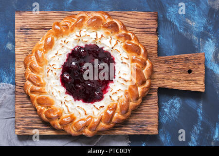 Pie with cottage cheese and berry jam close-up on a cutting board, top view - Stock Photo