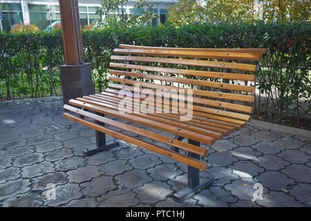 Wooden bench in the city park . Bench in the park among the trees . A wooden bench in the park, against a background of yellow fallen leaves lie on th - Stock Photo
