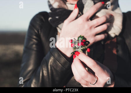 the girl holds a bouquet of red berries of cowberry in autumn time - Stock Photo