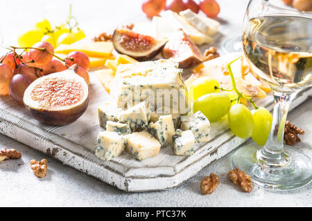 Cheese plate with grapes, figs and nuts.  - Stock Photo