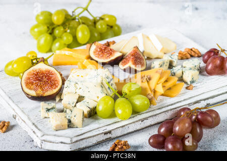 Cheese plate with grapes, figs and nuts. Wine snaks. Cheese assortment. - Stock Photo