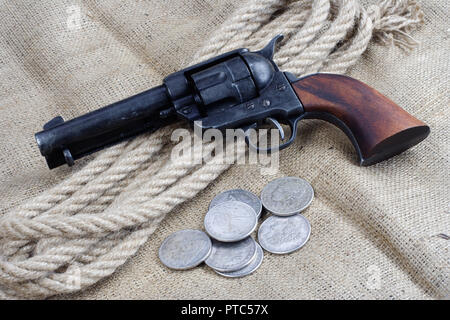 wild west revolver - colt single action army with silver dollars on canvas background - Stock Photo