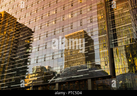 SEATTLE, WA, USA, - JUNE 2018: Reflections in a glass panelled office building in Seattle city centre at sunset. - Stock Photo