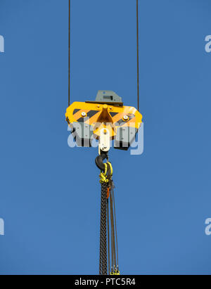 SEATTLE, WASHINGTON STATE, USA - JUNE 2018: Close up view of the pulley and hook of a tower cranes in Seattle city centre against a blue sky. - Stock Photo