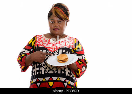 Studio shot of fat black African woman holding and pointing at b - Stock Photo