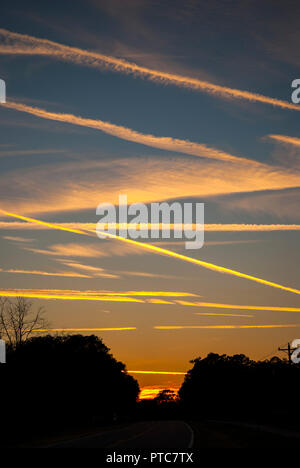 Jet contrails crisscross the skies at sunset in North Central Florida. - Stock Photo