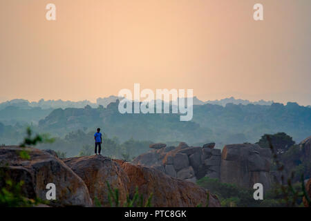 A single lone male climber stands on top of the popular bouldering rock with a golden hour back drop of hills and boulders. Hampi, India. - Stock Photo