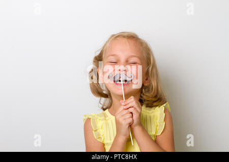 Free time for fun. Close up portrait small girl with fake mustache with plump - Stock Photo
