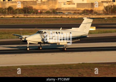 Beechcraft Super King Air 300 small private twin-engine turboprop commuter plane on the runway after landing in Malta at sunset - Stock Photo