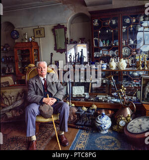 Swansea,Wales, Uk, May 24,1988: A smartly dressed elderly gentleman poses amid various antiques in his  shop on Dillwyn street, Swansea. - Stock Photo