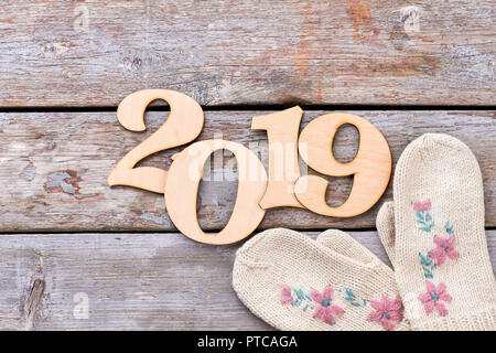 Wooden number 2019 and female mittens. Digit cut out number 2019 from wood and pair of white woolen gloves on rustic wooden background, top view. Happ - Stock Photo