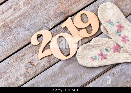 Carved wooden number 2019 and knitted mittens. Cut out wooden digit of New Year 2019 and pair of white woolen mittens with flower embroidery on old wo - Stock Photo