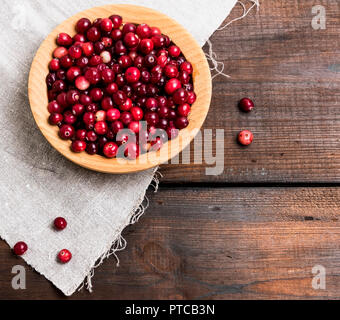 ripe red lingonberries in a wooden round bowl, top view, empty space - Stock Photo