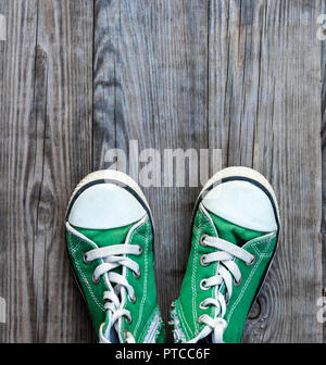 pairs of old textile green classic sneakers stand on a gray wooden background, top view, copy space - Stock Photo