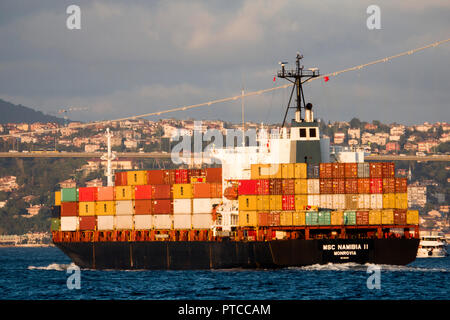 Container ship passing through the city along the Bosphorus in Istanbul, Turkey - Stock Photo