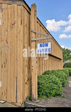 Now hiring sign hanging outside a commercial business indicating workers needed in Montgomery Alabama, USA. - Stock Photo