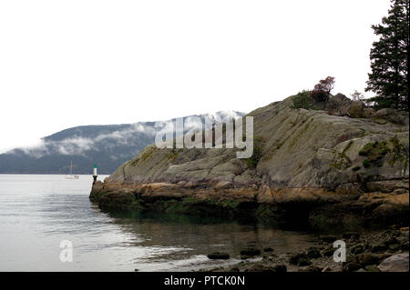 The rocky coast of Whytecliff Park, in West Vancouver, BC, Canada, on a rainy and cloudy day, showing the sea and a sailing ship in the background - Stock Photo