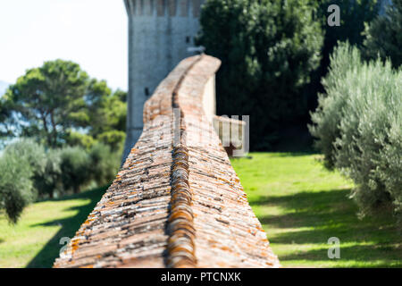 Castiglione del Lago medieval fortress closeup of fort tunnel wall in Umbria, Italy, Rocca with Medievale o Rocca del Leone tower, olive trees in sunn - Stock Photo