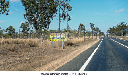 Large road train turning caution side on highway in central Queensland Australia - Stock Photo