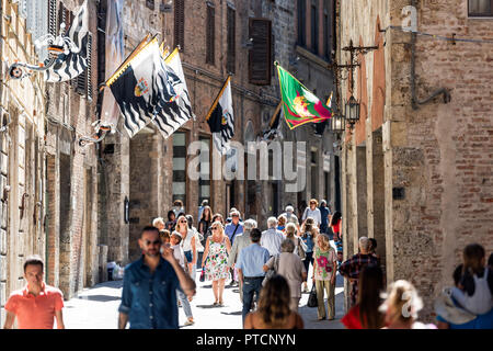 Siena, Italy - August 27, 2018: Street in historic medieval old town village in Tuscany with shopping stores, crowd of many people tourists walking, f - Stock Photo
