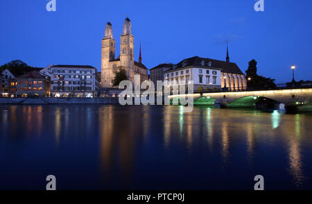 A view of the Grossmunster Tower along the Limmat at dusk in Zurich, Switzerland. - Stock Photo