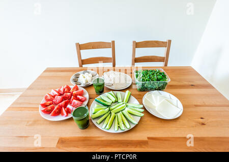 Wooden table with setting of healthy vegan vegetarian lunch or dinner, green vegetables, juice, cheese, salad, cucumbers, tomatoes, nobody in home apa - Stock Photo
