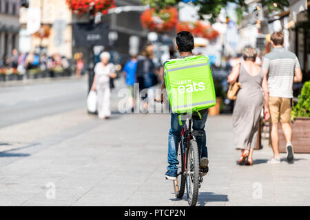 Warsaw, Poland - August 23, 2018: Uber eats bicycle man with green sign in old town historic street in capital city during sunny summer day called Kra - Stock Photo