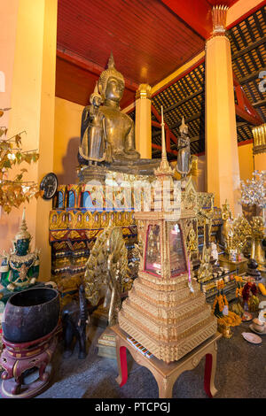 Altar with many golden Buddha statues and other items at the Wat Ong Teu Mahawihan (Temple of the Heavy Buddha), a Buddhist monastery, in Vientiane. - Stock Photo