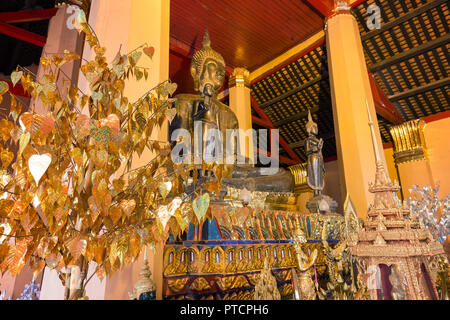 Altar with several golden Buddha statues and other items at the Wat Ong Teu Mahawihan (Temple of the Heavy Buddha), a Buddhist monastery, in Vientiane - Stock Photo