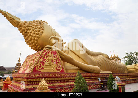 Large gilded Reclining Buddha statue at the Wat That Luang Tai Temple in Vientiane, Laos. - Stock Photo
