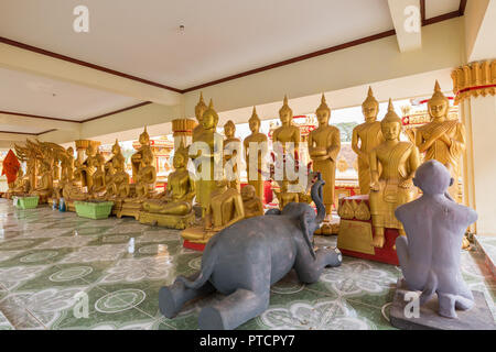 Two animal sculptures and many gilded Buddha statues at the Wat That Luang Tai Temple in Vientiane, Laos. - Stock Photo