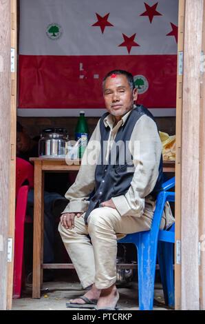 Nepalese man sitting in open room in Bhaktapur in Nepal - Stock Photo