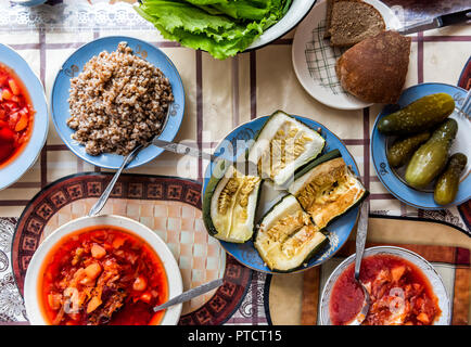 Flat top, high angle view down of table with setting of healthy vegan vegetarian lunch or dinner, green vegetables, salad, pickled cucumbers pickles,  - Stock Photo