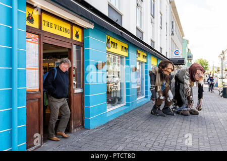 Akureyri, Iceland - June 17, 2018: Small town village city with people, street sidewalk in summer, man walking out of viking souvenir shop store - Stock Photo