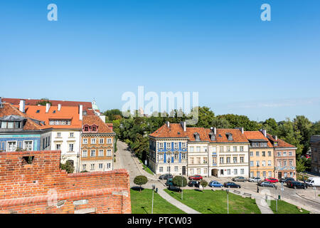 Warsaw, Poland - August 22, 2018: Famous old town historic street in capital city during sunny summer day, red orange brick wall, architecture - Stock Photo