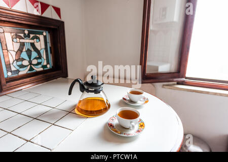 Two tea cups with black or green oolong tea herbal tea on white table with teapot pot in Italian villa rustic Tuscany home kitchen, sunlight - Stock Photo