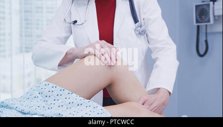 Young female woman having knee examined after sustaining injury in accident - Stock Photo