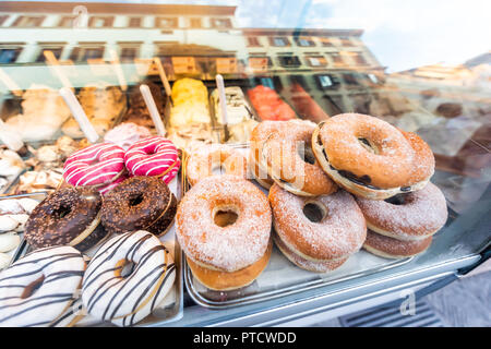 Many various assortment variety of chocolate, pink, sugar, plain, topped, icing and white donuts with sprinkles closeup on bakery tray, deep fried van - Stock Photo