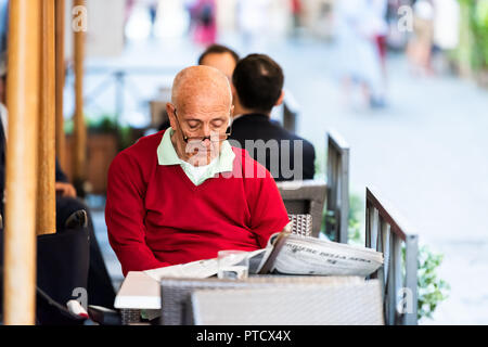 Rome, Italy - September 4, 2018: Closeup portrait of elderly senior Italian man in red sweater reading newspaper in street cafe in historic city in mo - Stock Photo