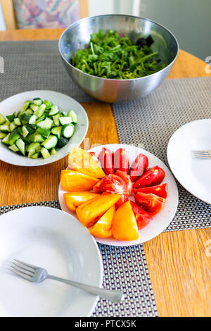 Wooden table with setting of healthy vegan vegetarian lunch or dinner, green vegetables, salad, cucumbers, cut tomatoes, nobody in home apartment mode - Stock Photo