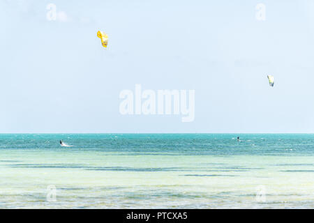 Key West, USA - May 1, 2018: Two men surfing, kitesurfing with kite on hydrofoil board in Florida at ocean, sea near beach, coast, coastline, in dista - Stock Photo