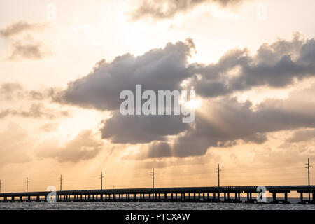 Overseas highway bridge road at Bahia Honda key state park during dramatic sunset with sun behind clouds, god rays, power electricity lines, water, wa - Stock Photo