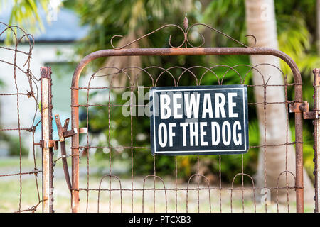 Beware of the dog sign on closed rusty fence gate with rust at residential neighborhood with house, home in background and nobody - Stock Photo